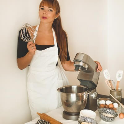 Femme utilisant un robot pâtissier
